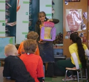 Puppeteer Chantal VanWierts demonstrates Toy Puppet Theatre to attentive 3rd graders